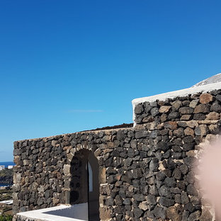 Inspiration for a huge mediterranean black split-level stone house exterior remodel in Catania-Palermo with a hip roof and a mixed material roof