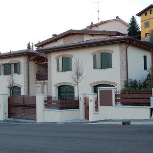 他の地域のカントリー風おしゃれな家の外観 (レンガサイディング、黄色い外壁、寄棟屋根、デュープレックス、瓦屋根) の写真