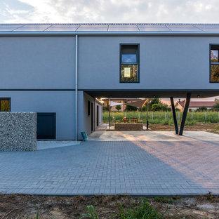 Idée de décoration pour une façade de maison grise design de taille moyenne et à un étage avec un revêtement en panneau de béton fibré, un toit à croupette et un toit en métal.