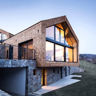 Immagine della facciata di una casa grande contemporanea a tre piani con rivestimenti misti e tetto a capanna