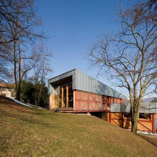 Immagine della facciata di una casa grande multicolore contemporanea a tre o più piani con rivestimento in legno e tetto a una falda