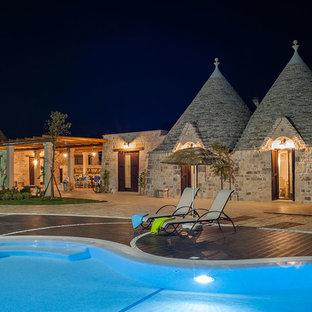 Immagine della facciata di una casa grande mediterranea a un piano con rivestimento in pietra