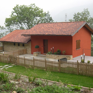 Immagine della facciata di una casa unifamiliare rossa country a un piano con rivestimenti misti, tetto a capanna e copertura in tegole