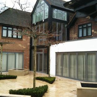 Diseño de fachada de casa multicolor, bohemia, grande, de tres plantas, con revestimientos combinados, tejado a cuatro aguas y tejado de teja de barro