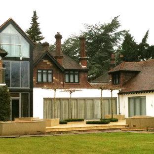 Modelo de fachada de casa multicolor, bohemia, grande, de tres plantas, con revestimientos combinados, tejado a cuatro aguas y tejado de teja de barro