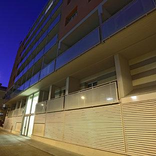 Diseño de fachada de piso naranja, moderna, grande, de tres plantas, con revestimientos combinados y tejado plano