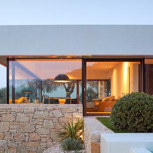 Idee per la facciata di una casa bianca stile marinaro di medie dimensioni con rivestimento in pietra e tetto piano