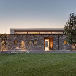 Immagine della facciata di una casa contemporanea a un piano con rivestimento in pietra e tetto piano