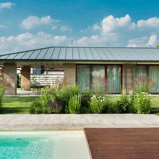 Immagine della facciata di una casa beige contemporanea a un piano di medie dimensioni con rivestimento in pietra e tetto a capanna