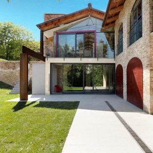 Ispirazione per la facciata di una casa grande marrone in campagna a due piani con rivestimento in mattoni e tetto a capanna