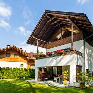 Esempio della villa bianca rustica a tre piani con rivestimento in stucco e tetto a capanna
