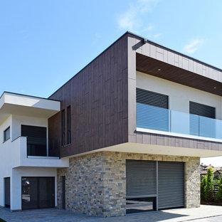 Ispirazione per la facciata di una casa moderna a due piani con rivestimento in pietra e tetto piano