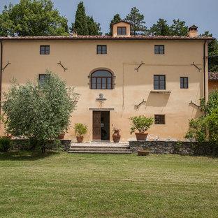 Ispirazione per la facciata di una casa unifamiliare gialla mediterranea con tetto a capanna e copertura in tegole