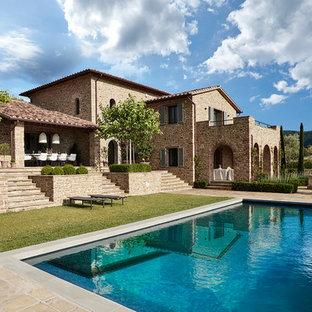 Immagine della facciata di una casa unifamiliare mediterranea a due piani con rivestimento in pietra, tetto a capanna e copertura in tegole