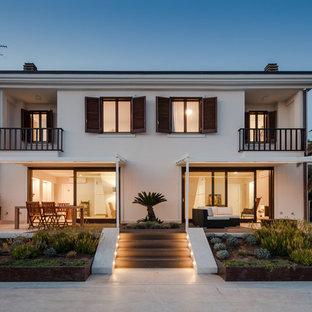 Esempio della facciata di una casa unifamiliare bianca stile marinaro a due piani di medie dimensioni con rivestimento in stucco e tetto piano