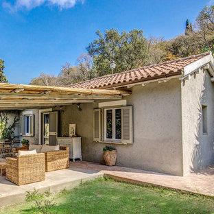 Modelo de fachada de casa beige, campestre, de tamaño medio, de una planta, con tejado a dos aguas y tejado de teja de barro