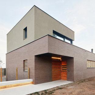 Diseño de fachada beige, urbana, de tamaño medio, de dos plantas, con revestimiento de ladrillo y tejado plano