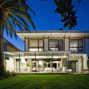 Imagen de fachada de casa blanca, contemporánea, grande, de dos plantas, con revestimientos combinados y tejado de un solo tendido