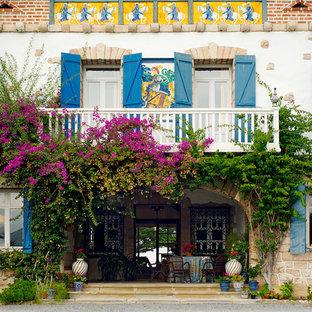 Imagen de fachada mediterránea, grande, de tres plantas, con revestimientos combinados