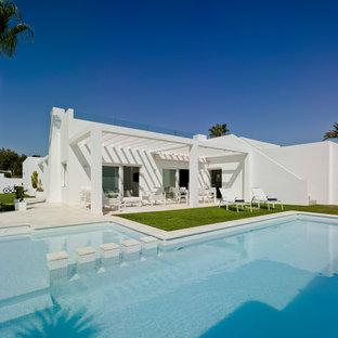 Imagen de fachada de casa blanca, actual, de tamaño medio, de una planta, con revestimiento de estuco y tejado plano