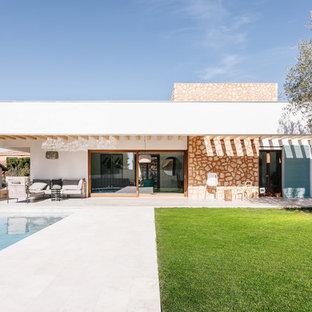 Diseño de fachada de casa blanca, mediterránea, de una planta, con tejado plano y revestimiento de piedra