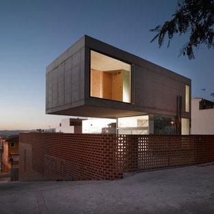 Esempio della facciata di una casa grande grigia contemporanea a piani sfalsati con rivestimento in cemento e tetto piano