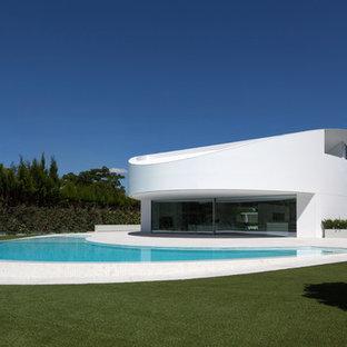 На фото: двухэтажный, белый, огромный дом в современном стиле с облицовкой из цементной штукатурки