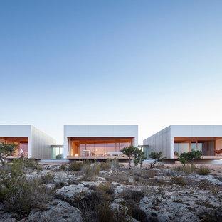 Ejemplo de fachada de casa gris, moderna, de tamaño medio, de dos plantas, con revestimiento de madera, tejado plano y tejado de varios materiales