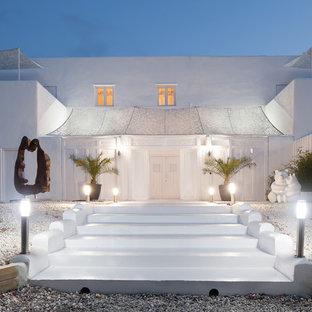 Foto de fachada de casa blanca, costera, grande, de dos plantas, con revestimiento de estuco y tejado plano
