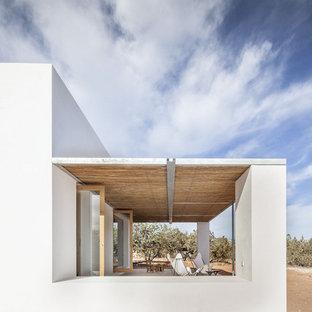 Imagen de fachada de casa blanca, mediterránea, pequeña, de una planta, con revestimientos combinados, tejado plano y tejado de varios materiales