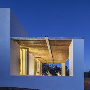 Ejemplo de fachada de casa blanca, mediterránea, pequeña, de una planta, con revestimientos combinados, tejado plano y tejado de varios materiales