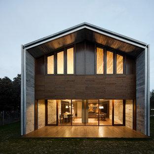 Diseño de fachada marrón, contemporánea, grande, de dos plantas, con revestimientos combinados y tejado a dos aguas