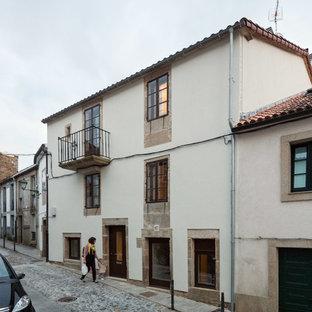Foto de fachada blanca, mediterránea, de tamaño medio, de tres plantas, con revestimientos combinados y tejado a dos aguas