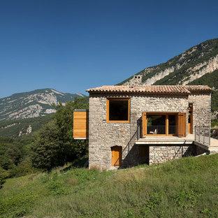 Ejemplo de fachada gris, rural, de tamaño medio, de dos plantas, con revestimiento de piedra y tejado a dos aguas