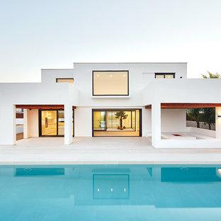 Diseño de fachada blanca, mediterránea, de tamaño medio, de dos plantas, con tejado plano y revestimiento de estuco