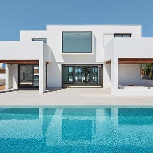 Foto della facciata di una casa bianca mediterranea a due piani di medie dimensioni con rivestimento in stucco e tetto piano