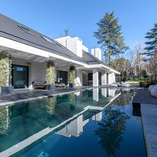 Large transitional white one-story concrete exterior home photo in Madrid with a hip roof