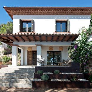 Modelo de fachada de casa blanca, mediterránea, grande, de dos plantas, con revestimientos combinados, tejado a cuatro aguas y tejado de teja de barro