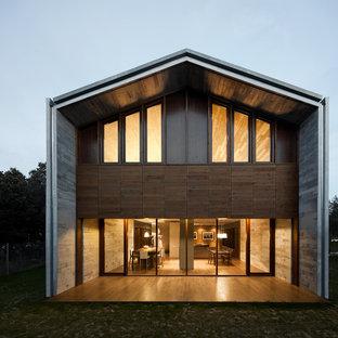 Diseño de fachada gris, urbana, grande, de dos plantas, con revestimientos combinados y tejado a dos aguas