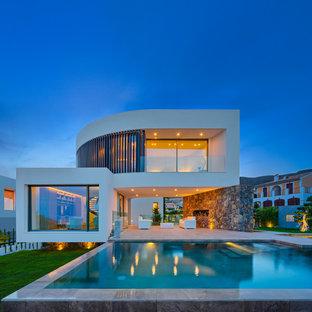 Ejemplo de fachada blanca, contemporánea, grande, de dos plantas, con revestimientos combinados y tejado plano