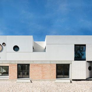 Ejemplo de fachada de casa blanca, urbana, de tamaño medio, de tres plantas, con revestimientos combinados, tejado plano y tejado de varios materiales