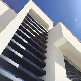 Неиссякаемый источник вдохновения для домашнего уюта: четырехэтажный, белый таунхаус среднего размера в современном стиле с облицовкой из цементной штукатурки, плоской крышей и крышей из смешанных материалов