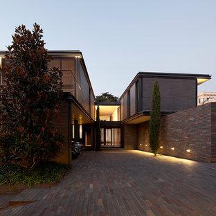 Diseño de fachada marrón, actual, grande, de dos plantas, con revestimiento de ladrillo y tejado plano