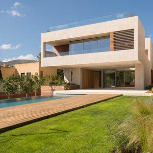 Modelo de fachada de casa beige, minimalista, grande, de dos plantas, con revestimiento de piedra y tejado plano