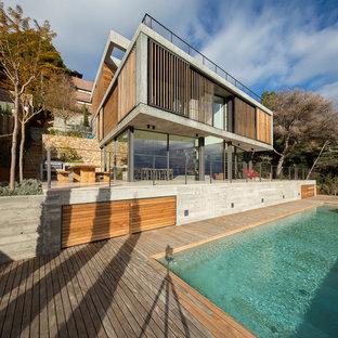 Ejemplo de fachada de casa gris, moderna, grande, a niveles, con revestimiento de hormigón y tejado plano