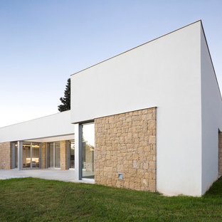 Diseño de fachada de casa blanca, actual, grande, de una planta, con tejado plano y revestimientos combinados