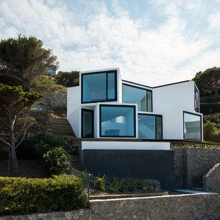 Diseño de fachada blanca, actual, de tamaño medio, de dos plantas, con revestimiento de estuco y tejado plano