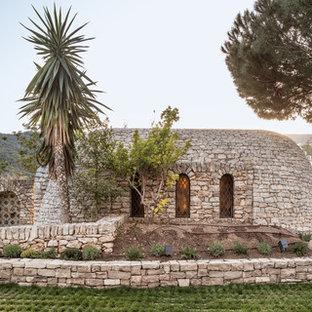 Diseño de fachada gris, mediterránea, de una planta, con revestimiento de piedra