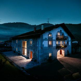 Cette photo montre une façade de maison grise montagne à deux étages et plus avec un toit à deux pans et un toit en tuile.