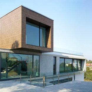 Ejemplo de fachada gris, actual, de tamaño medio, a niveles, con revestimiento de hormigón y tejado plano
